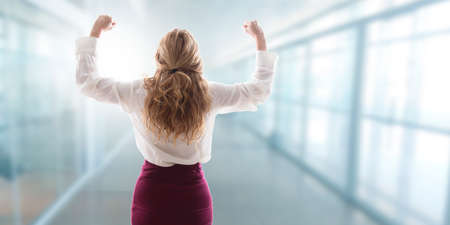 woman in the office with arms aloft celebrating success