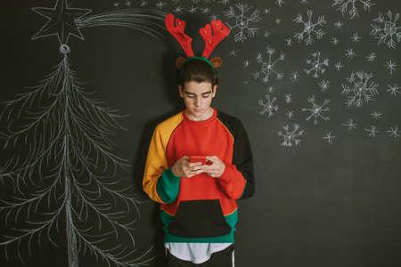 giovane con cellulare e sfondo e decorazioni natalizie Archivio Fotografico