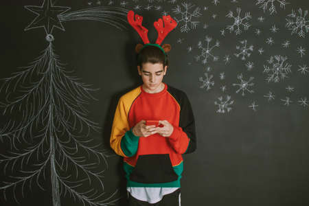 young with mobile phone and background and christmas decoration