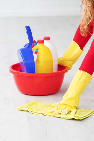 hand with cleaning products scrubbing the floor
