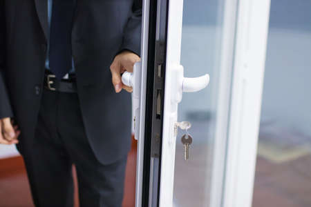 hand at the entrance door or access, lock and security Stock Photo