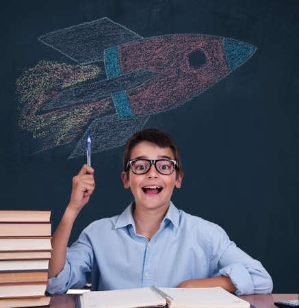 Schüler mit Ideenausdruck und Rakete an der Tafel