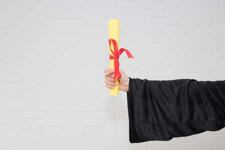 hand with graduation diploma