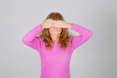 woman covering her eyes with hands on bottom