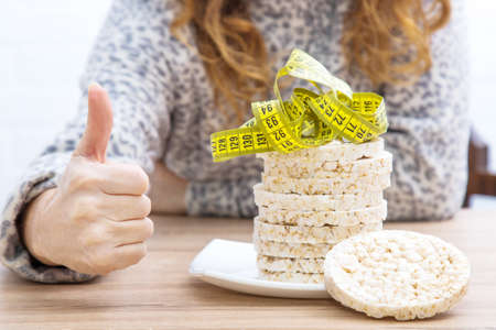 diet and slimming concept, corn cakes with tape measure and girl Banco de Imagens