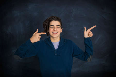 portrait of smiling teenager pointing