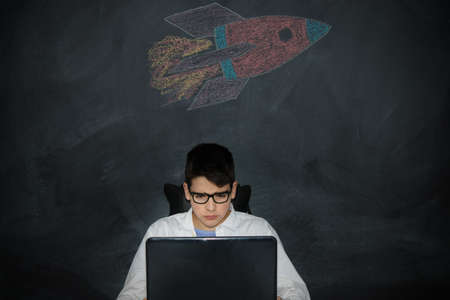 student with computer and spacecraft or rocket