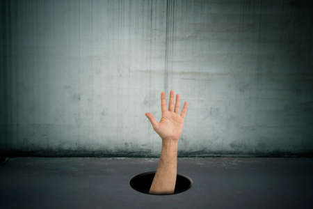 hand asking for help in the hole