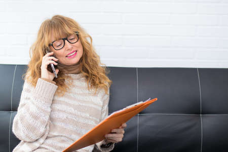 adult woman with mobile phone and documents at home or in the office