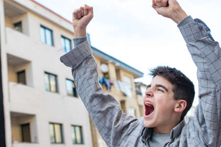 teen or student screaming and celebrating outdoors