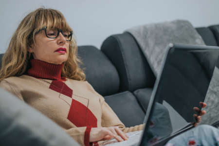 woman with laptop on the couch 写真素材