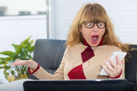 surprised woman watching the phone 写真素材