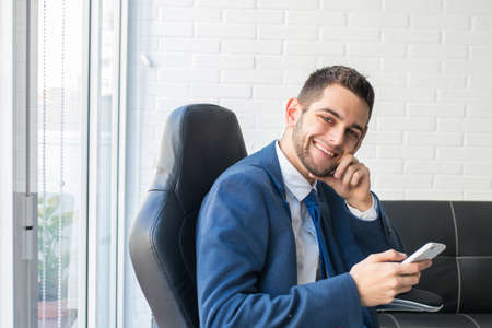 businessman smiling with cell phone in the office