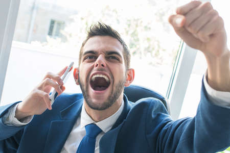 businessman triumphant with phone and celebrating success
