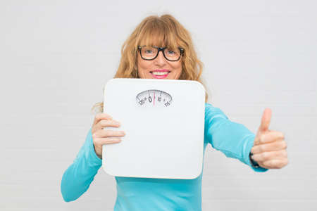 woman with scales, concept of diet and beauty Stock Photo