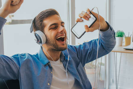 man with mobile phone and singing headphones