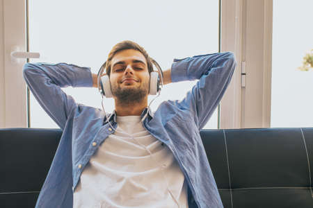 young man listening to music at home with headphones