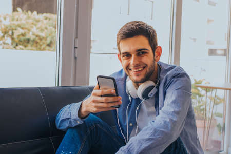 young man with mobile phone at home