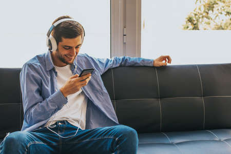 fashionable young man with mobile phone and earphones on the couch Stockfoto