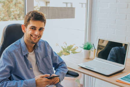 young man with mobile phone and laptop at home