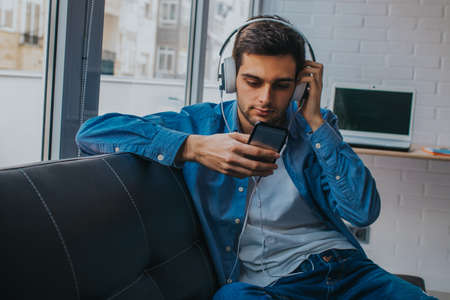 man at home with mobile phone and earphones Stockfoto