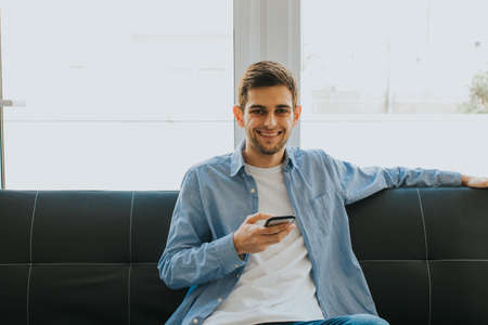 young man or teenager with mobile phone indoors