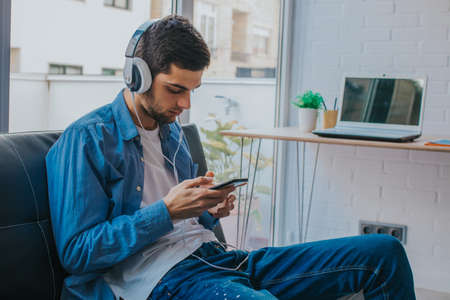 young man or teenager with mobile phone and headphones at home