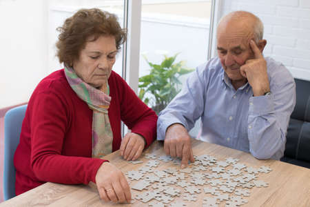 older couple making puzzle on the table