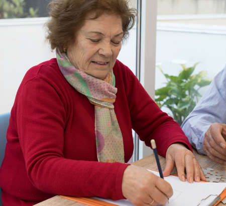 older adult woman writing Banque d'images