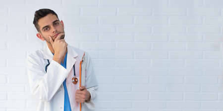 doctor thinking about white brick background Stock Photo