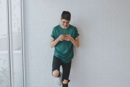 student or young teenager with mobile phone on the wall supported