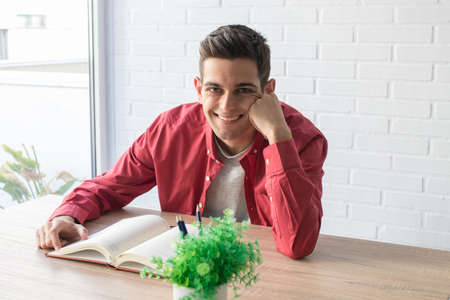 young man or student at home with the book