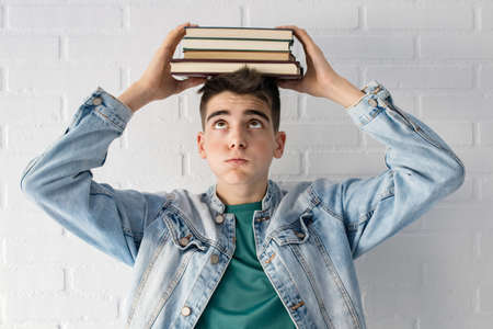 student with expression of burden and stress with books piled on the head