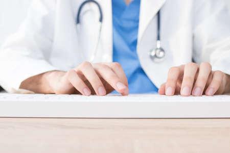 Arzthände tippen in den Computer