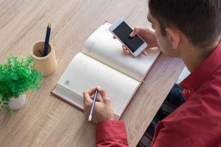 junge Hand mit Handy und Notizblock oder Buch