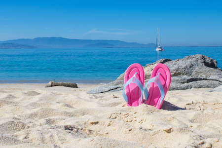 sandals in the sand of the beach in summer