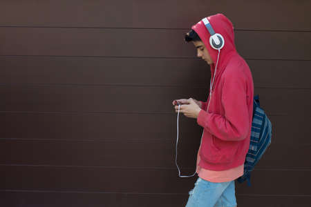 young man or student with mobile phone and headphones outdoors