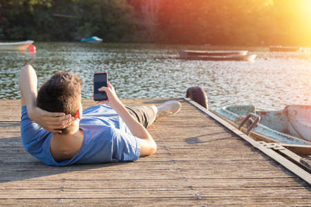young man with mobile phone at sunset outdoors