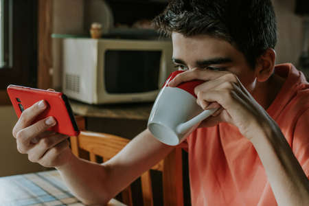 young man having breakfast or drinking coffee with mobile phone