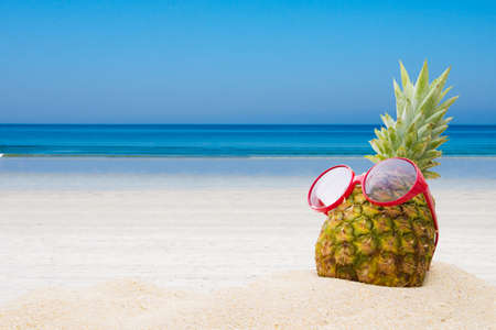 pineapple with sunglasses on the beach Stock fotó