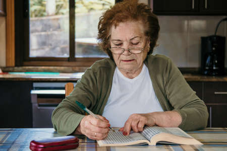 portrait of an older woman reading or with the crossword at home