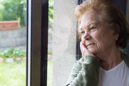 older woman looking out the pensive window, seniors