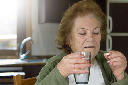 older woman with medications and pills