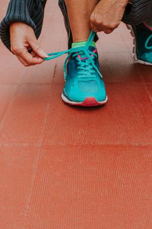 closeup of hands tying the running shoe