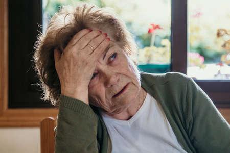 portret van een oudere vrouw met hoofdpijnuitdrukking