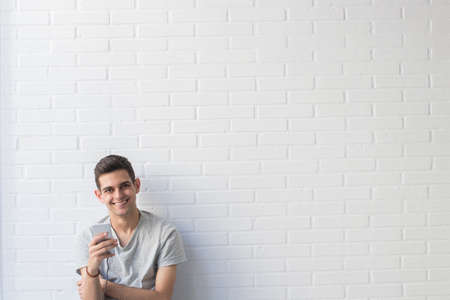 young man with mobile phone on white brick background Stock Photo