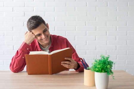 young man or student with the book on the table