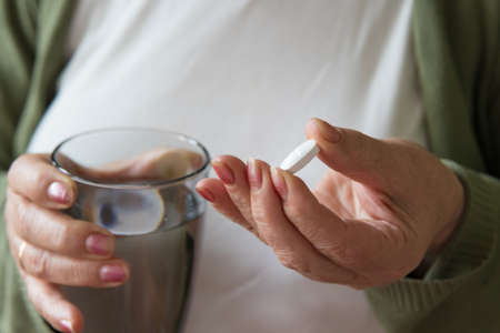 senior hand with pills and glass of water