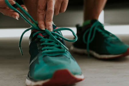 runner tying his shoe to do sports Reklamní fotografie - 132123709