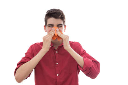 isolated young boy sneezing with handkerchief